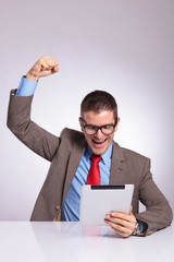 young business man cheers with tablet