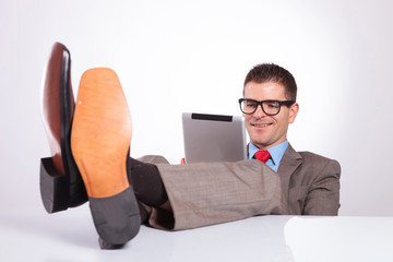 young business man smiles at tablet, with feet on desk