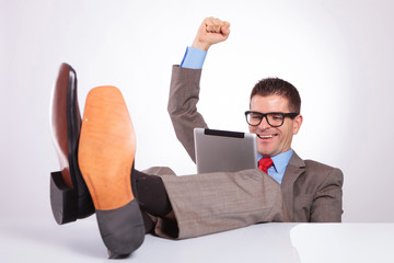 young business man cheers with tablet and feet on desk