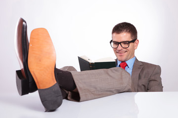 young business man reads a book with feet on desk