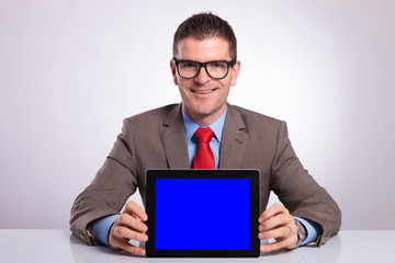 young business man holds a tablet at his desk