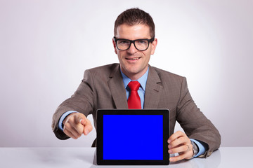 young business man presents tablet and points at you