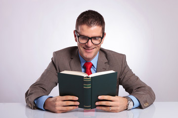 young business man holds book with both hands