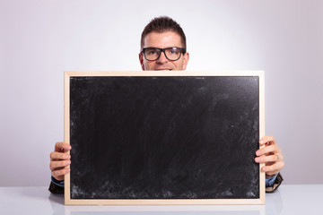 young business man looks at you from behind blackboard