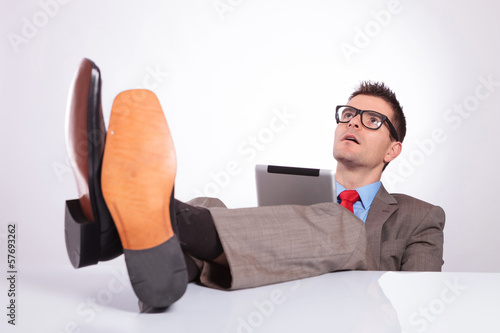 young business man looks up with feet on desk