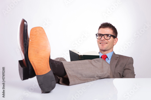young business man reads with feet on desk