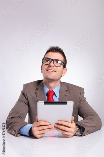 young business man with tablet looks up and smiles