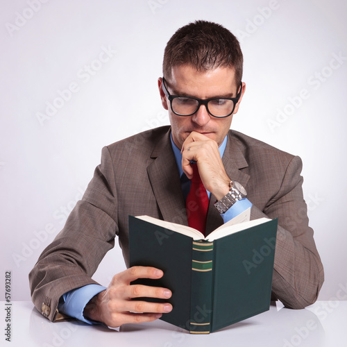 young business man reading a book at his desk