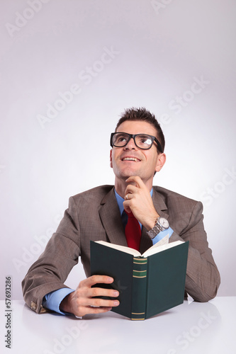 young business man with book in hand is daydreaming