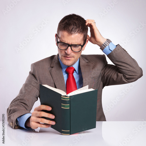 young business man reads a book and scratches his head