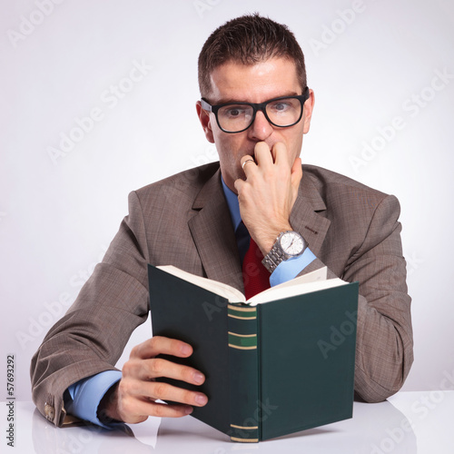 young business man reads a scary book