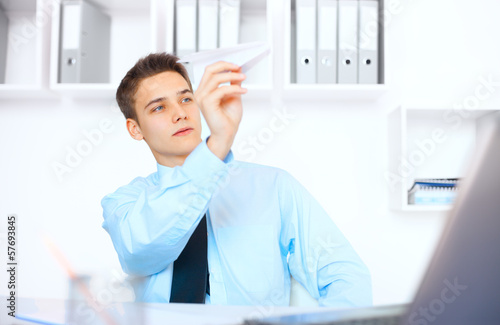 Young businessman launch a paper airplane