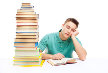 Young tired student sitting at the desk with high books stack
