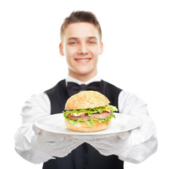 Young happy smiling waiter holding hamburger on plate