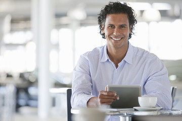 Portrait of smiling man drinking coffee and using digital tablet at cafe table