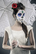 Day of the dead girl with sugar skull make-up holding umbrella