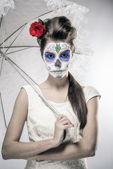 Day of the dead girl with sugar skull makeup holding umbrella