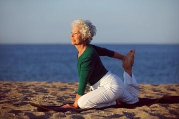 Senior woman doing yoga by the ocean