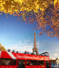 Eiffel Tower against tourist red bus in Paris, France