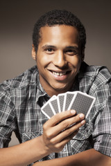 smiling dark-skinned young man holding playing cards