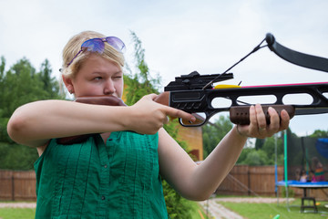 A girl with a crossbow in hands aiming at a target