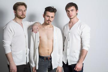 Three men in cardigan over his naked body in studio