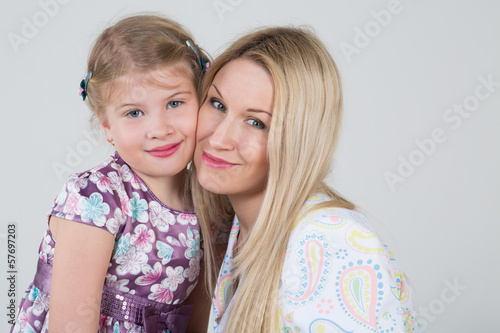 A tender portrait of a mother and daughter huddled together