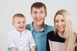Happy smiling family of three in studio