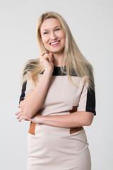 Beautiful smiling girl in a beige dress in the studio