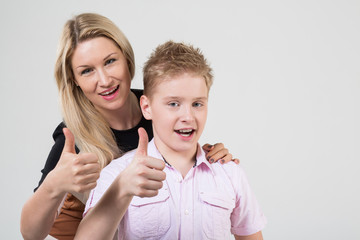 Mother and son with blond hair doing thumbs up