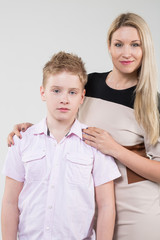 The mother in a beige dress hugging son