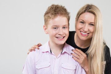 Happy mother hugging smiling son in the studio