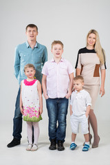 Happy modern family of five people in the studio