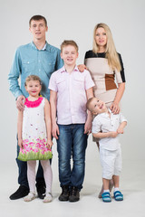 family of five people, youngest son looks up in studio