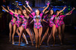 Nine showgirls in costumes with raised hands perform