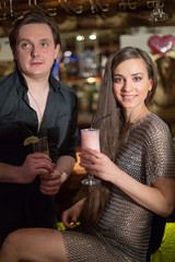 man in shirt and girl in chaindress with cocktails in the bar