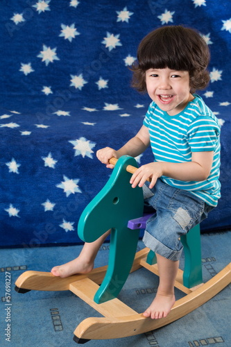 little boy have fun on toy horse in room with blue sofa