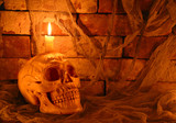 Human skull with candle in tomb
