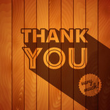 Thank you card with typography on a wooden background.