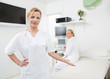 Gynecologist Gesturing With Colleague In Background