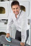 Businessman Ironing Jeans In Laundry