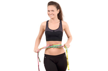 Fit girl measuring her waist with three measuring tapes.