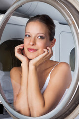 Beautiful Woman Looking Through Washing Machine Door
