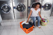 Woman With Baskets Of Dirty Clothes Sitting At Laundromat