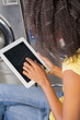 Young Woman Using digital Tablet In Laundry