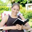 Frau liest Buch im Garten
