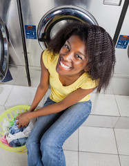 Woman With Laundry Basket Near Washing Machines