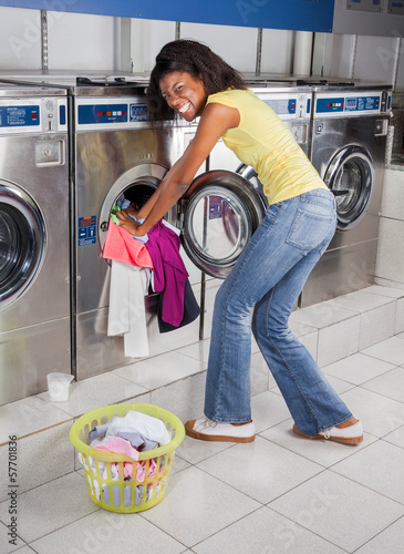 Woman Pushing Clothes In Washing Machine