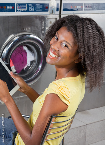 Woman Holding Digital Tablet Sitting At Laundromat