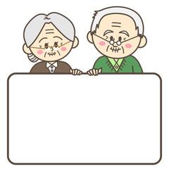 ホワイトボードを持つ老夫婦